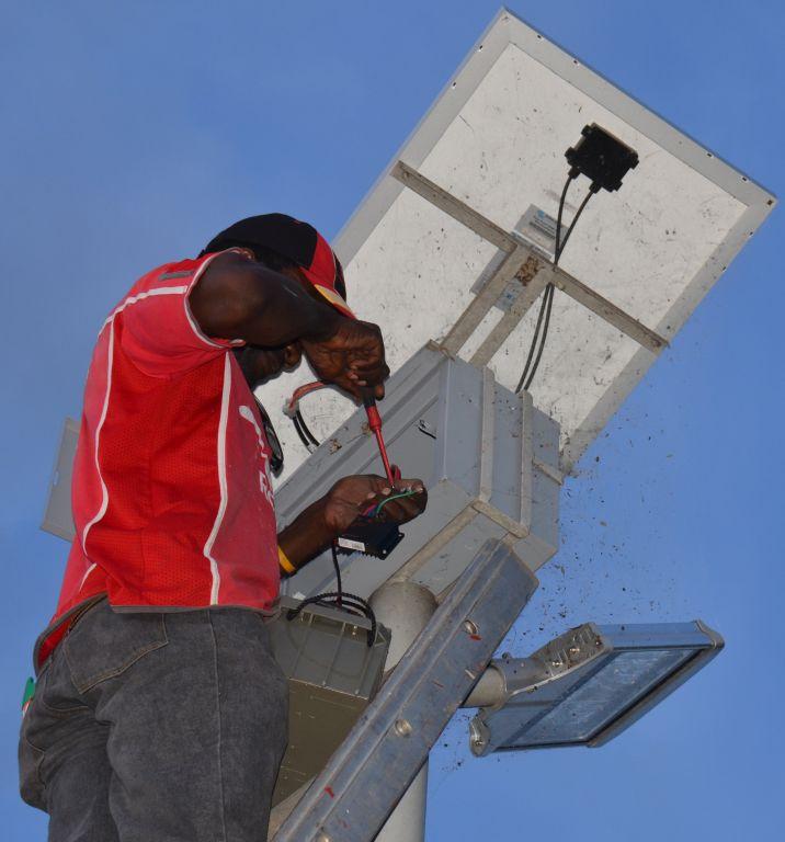 George Mubiana repairs the solar streetlights